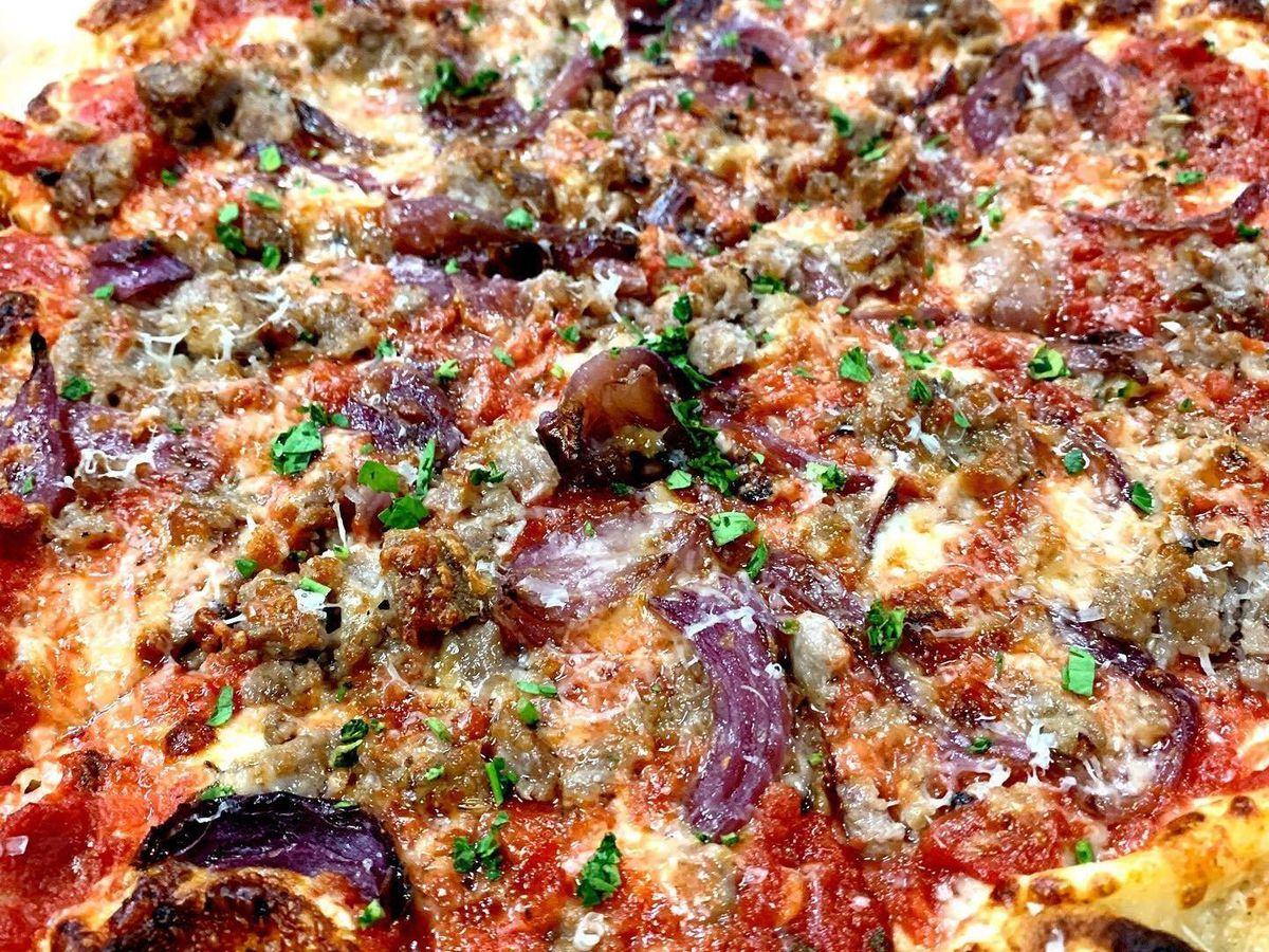 A pizza topped with onion, meat, and herbs