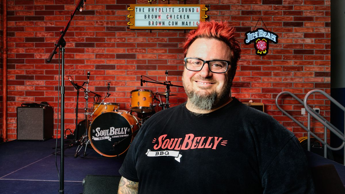 A man with red hair stands in front of a stage