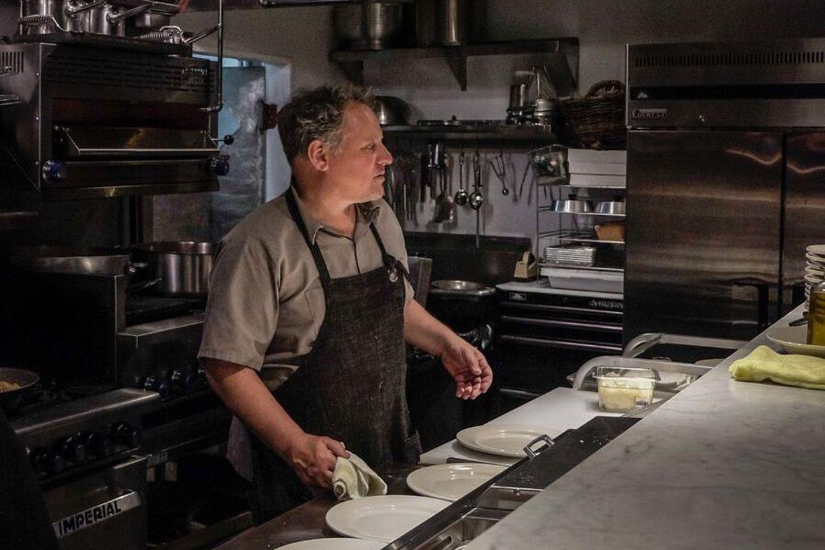 Chef Chris Bianco at work inside a dark kitchen.