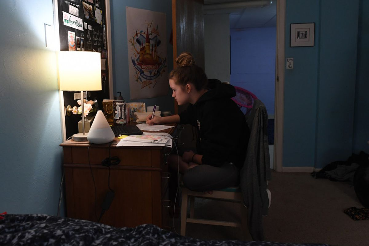 A student engages in remote learning from her bedroom, using a lamp to light her work.