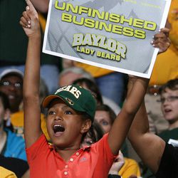 Elizabeth Green, 9, watches large video monitors in Waco, Texas, as Baylor takes on Notre Dame in the NCAA women's college basketball tournament Final Four championship game in Denver, Tuesday, April 3, 2012. Hundreds of fans gathered inside the Ferrell Center to watch the game. (AP Photo/Waco Tribune-Herald, Duane A. Laverty)