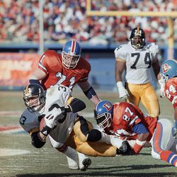 Pittsburgh Steelers Merril Hoge (33) is brought down from behind by Denver Broncos Steve Atwater (27) and Greg Kragen (71) during the first quarter of the AFC playoff game in Denver, Jan. 7, 1990.