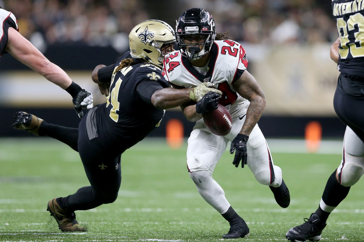 Atlanta Falcons running back Devonta Freeman nearly fumbles the ball against New Orleans Saints defensive end Cameron Jordan in the first quarter at the Mercedes-Benz Superdome.