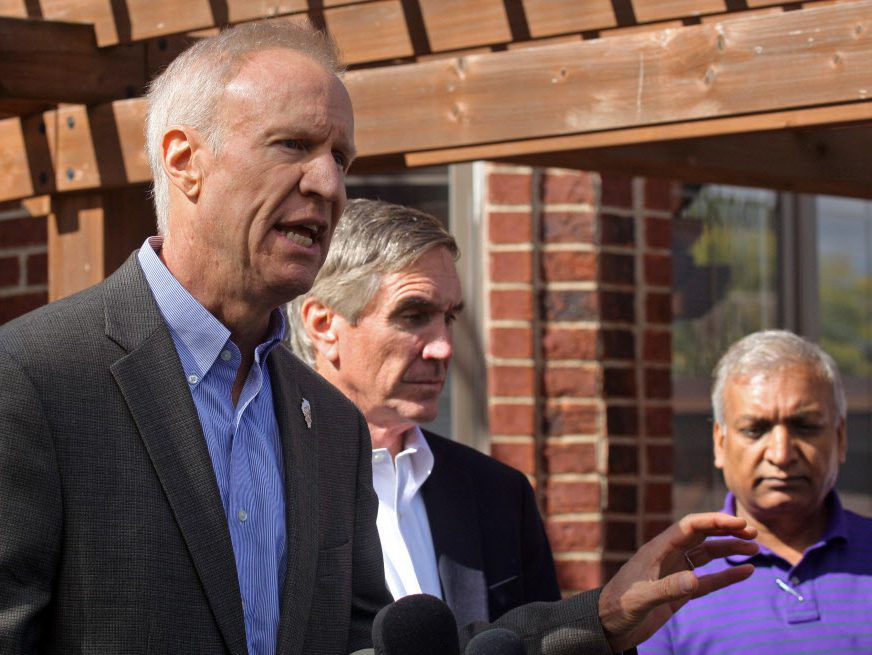 Gov. Bruce Rauner speaks in the backyard at a home in Des Plaines, Illinois, Thursday. Standing next to him is Illinois Republican Chairman Timothy Schneider. Tim Boyle/For the Sun-Times