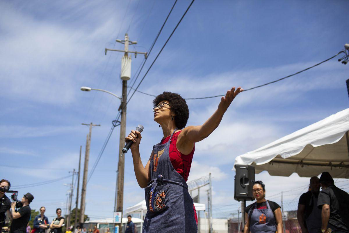 Jocelyn Jackson holding a microphone as she gives a speech outside.
