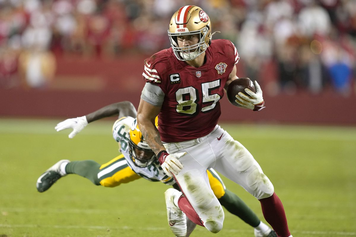 George Kittle #85 of the San Francisco 49ers runs with the ball after catching a pass against the Green Bay Packers during the fourth quarter in the game at Levi's Stadium on September 26, 2021 in Santa Clara, California.