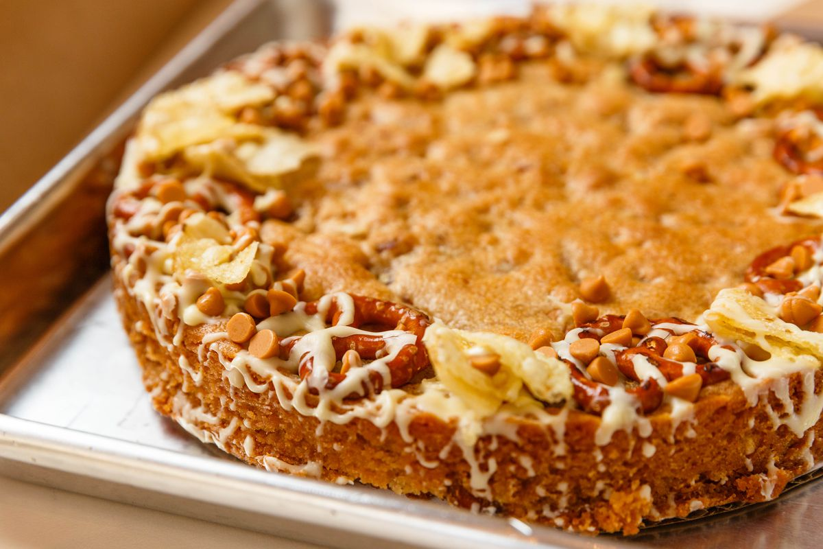 A big cookie cake with pretzels and potato chips, in a metal sheet pan at Milk Bar