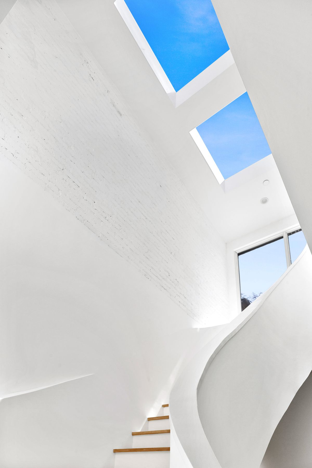A white curved staircase with two skylights at the top.