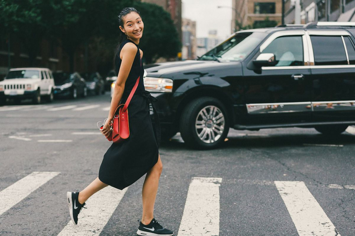 A woman in a black dress, black Nike sneakers, and a red purse crossing the street in New York City.