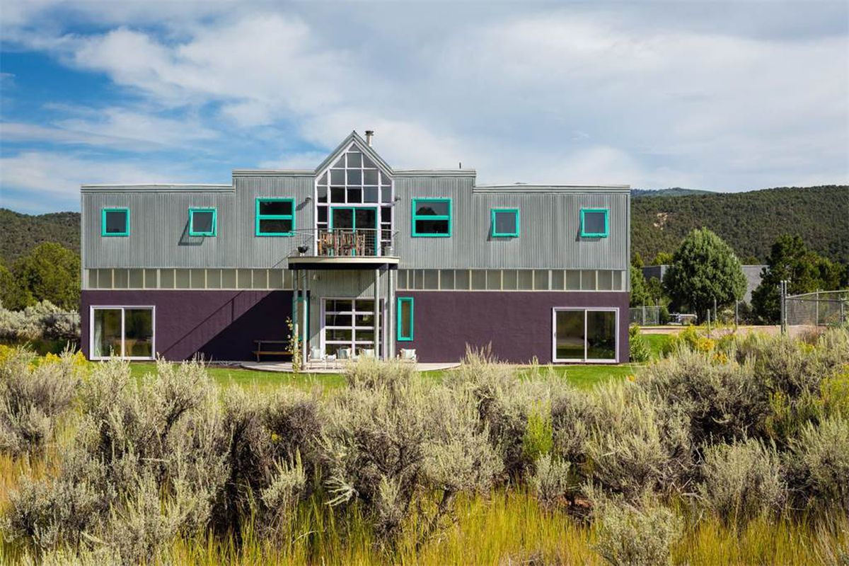 Exterior shot of a two-story structure features a metal-clad facade on the upper level punctuated by small square windows framed in turquoise. The facade of the lower level is painted purple, and a strip of translucent windows runs horizontally between th