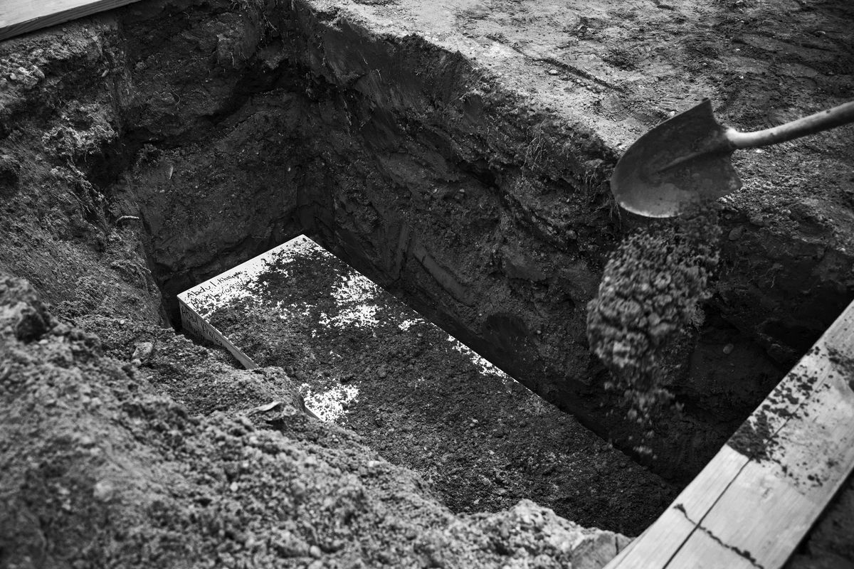 A casket that has been lowered into the grave, and is covered with dirt.