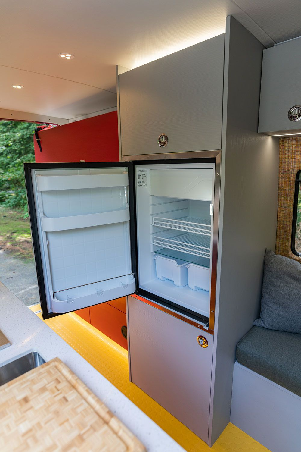 A gray cabinet in the camper van features a large fridge at standing height.