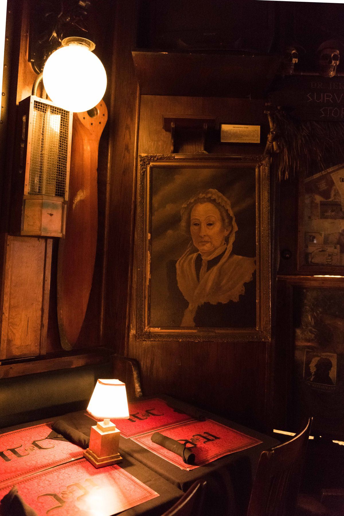 An old portrait looks over a dining table.