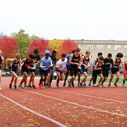 Runners from several CPS schools set their watches as they start their race at the meet at River Park.