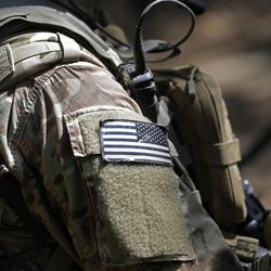 In this photo taken Friday, April 21, 2017 a United States flag patch adorns the uniform of a paratrooper with the 82nd Airborne Division's 3rd Brigade Combat Team during a training exercise at Fort Bragg, N.C. The Army is planning to triple the amount of bonuses it's paying this year to more than $380 million in a bid to expand its ranks. The money includes new incentives to woo reluctant soldiers to re-enlist.