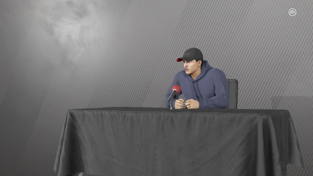 a hockey player wearing a dark blue hoodie and baseball cap sitting behind a black table in NHL 21