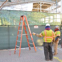 """New decorative """"ivy"""" tarp being installed at the top of the fence on Waveland"""