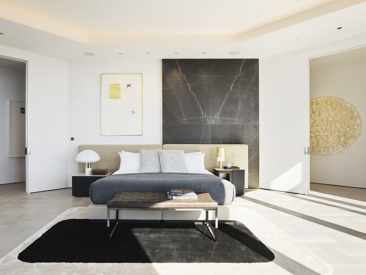 A large bed with a black rectangular rug in front.