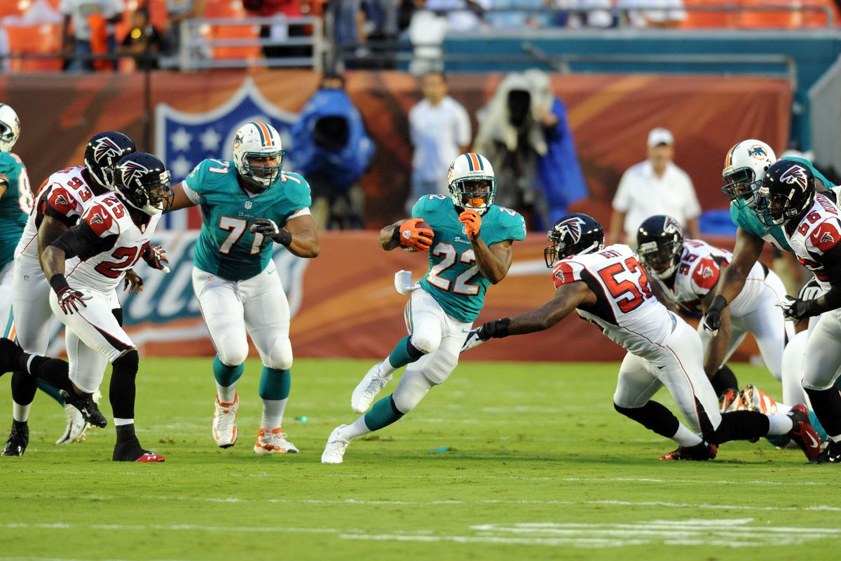 Aug. 24, 2012; Miami, FL, USA; Miami Dolphins running back Reggie Bush (22) runs past Atlanta Falcons linebacker Akeem Dent (52) during the first quarter at Sun Life Stadium. Mandatory Credit: Steve Mitchell-US PRESSWIRE