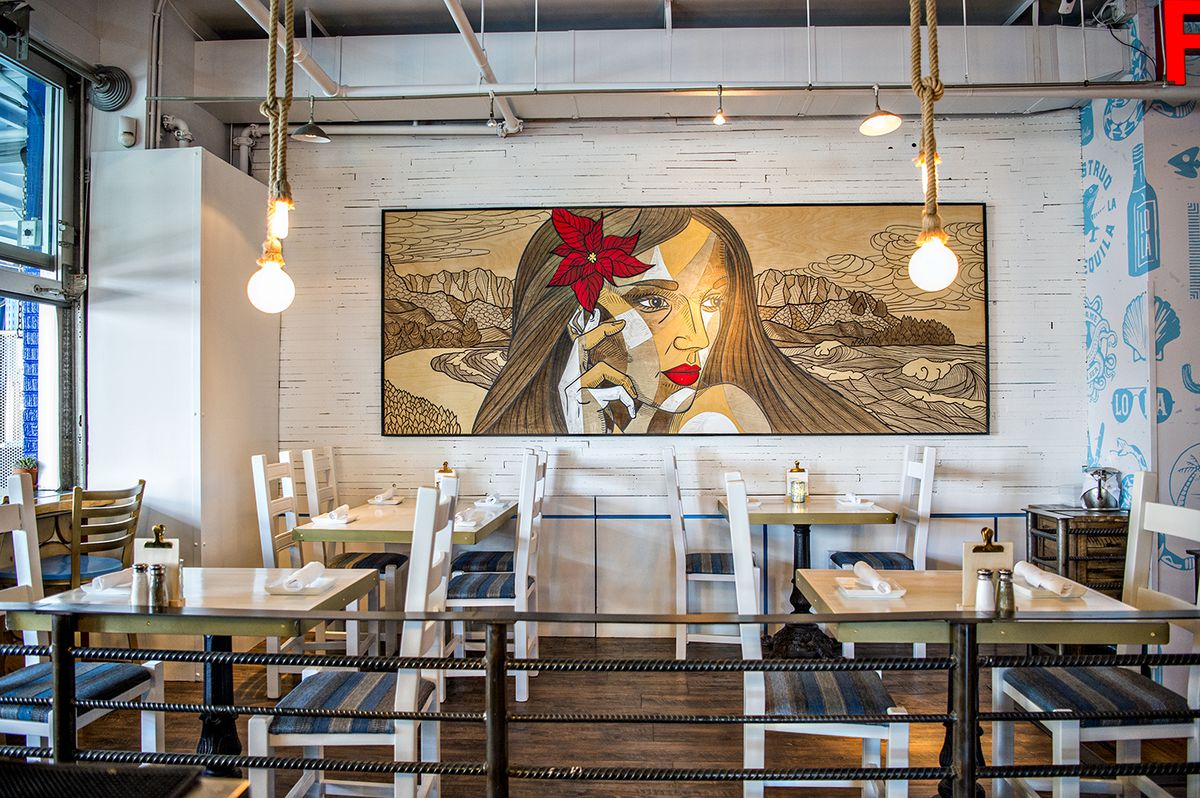 The section of tables leading toward the outdoor patio features a mural of a woman with a red flower in her hair.