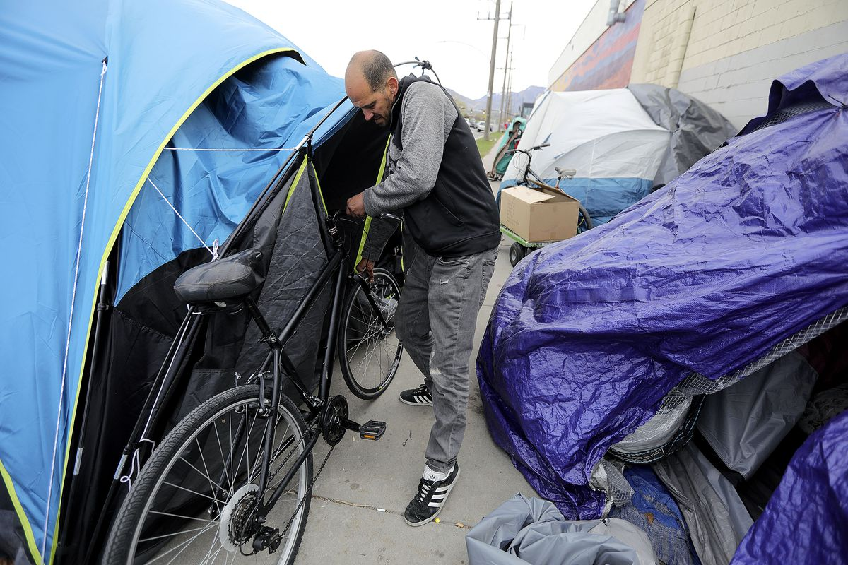 Andrew Blackburn, who has been homeless for about a year, steadies a bike that blew over in the wind against a neighbor's tent on 800 South in Salt Lake City on Tuesday, April 13, 2021.