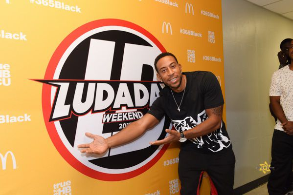 """Rapper Ludacris standing in front of a """"Ludaday Weekend"""" banner."""