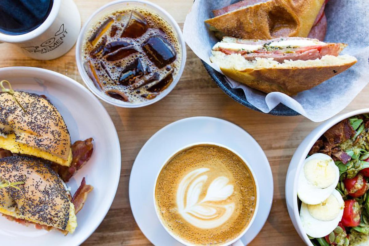 Overhead view of a table full of cafe items, including a bagel sandwich, a salad, and hot and iced coffees