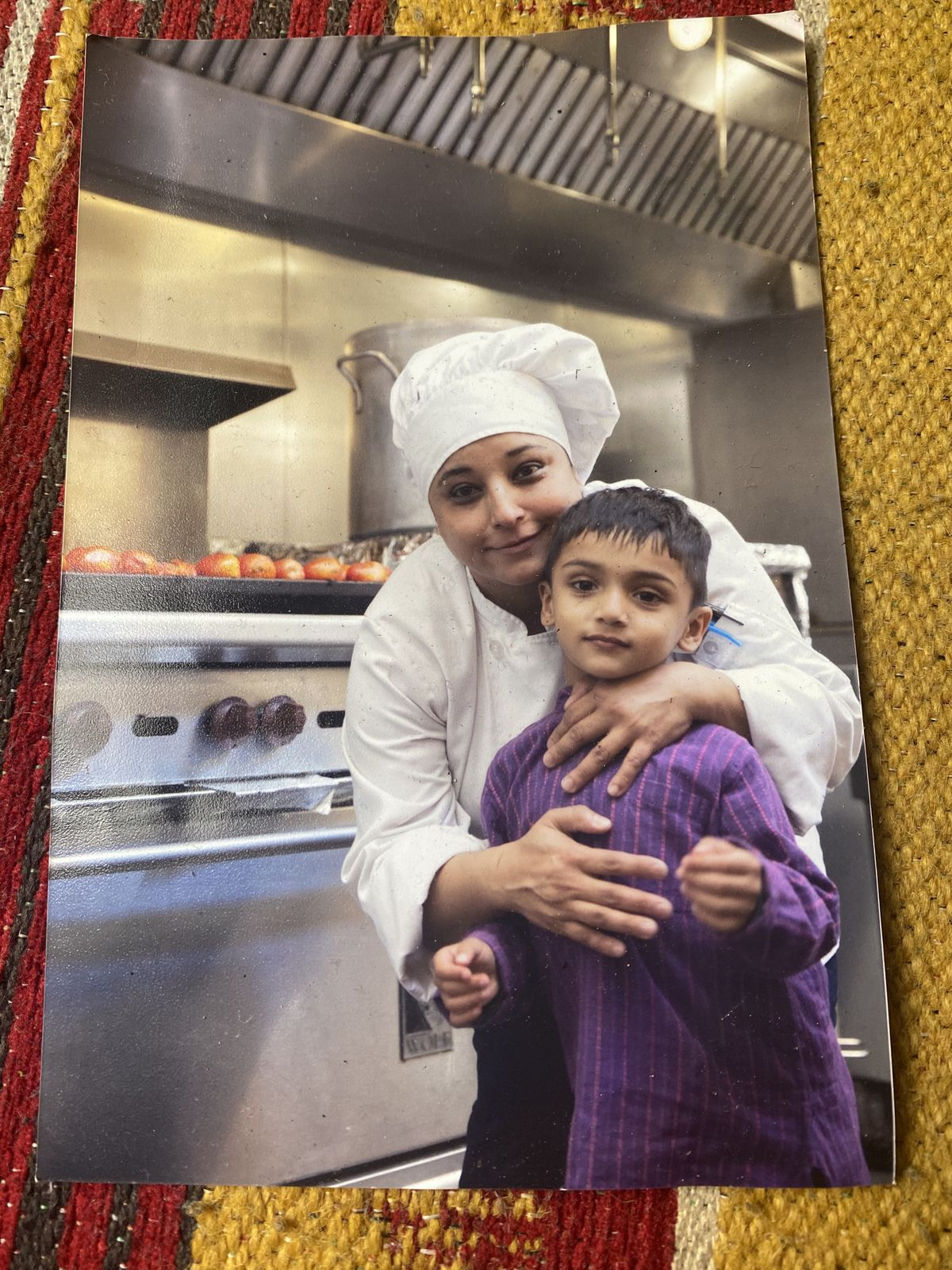 Bini Pradhan in the kitchen, wearing her chef's whites, with her son Ayush