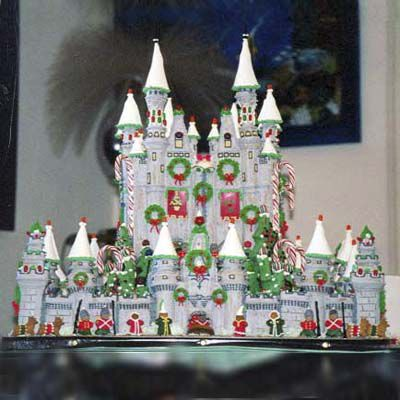 Detailed white gingerbread castle decorated with green wreaths made of icing.