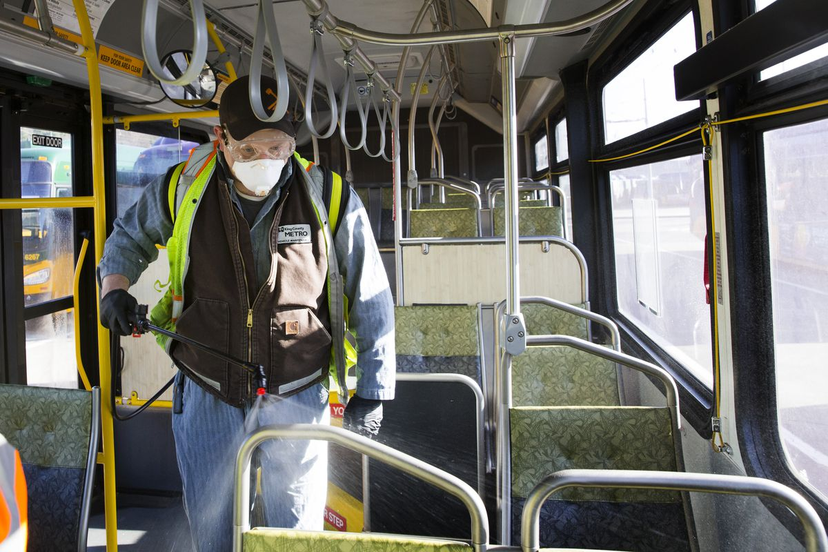 A masked equipment service worker for King County Metro sprays a disinfectant through a bus in Seattle, Washington.