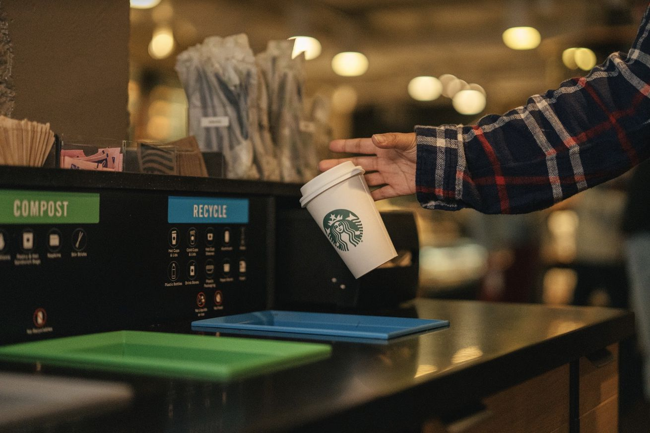 A customer discards a Starbucks cup in a recycling bin