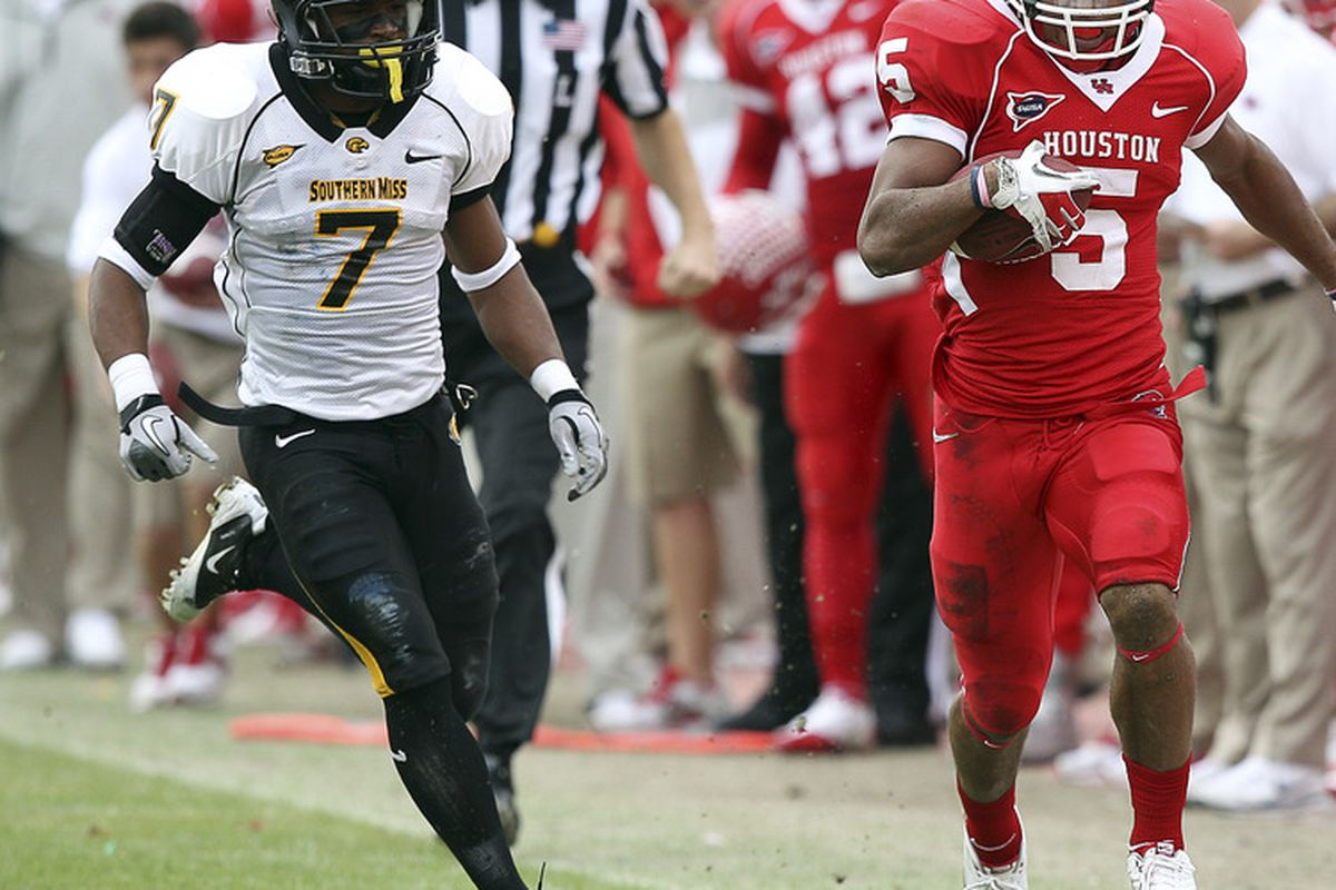 HOUSTON - DECEMBER 03:  Running back Charles Sims #5 of the Houston Cougars runs past Deron Wilson #7 of the Southern Miss Golden Eagles at Robertson Stadium on December 3, 2011 in Houston, Texas.  (Photo by Bob Levey/Getty Images)