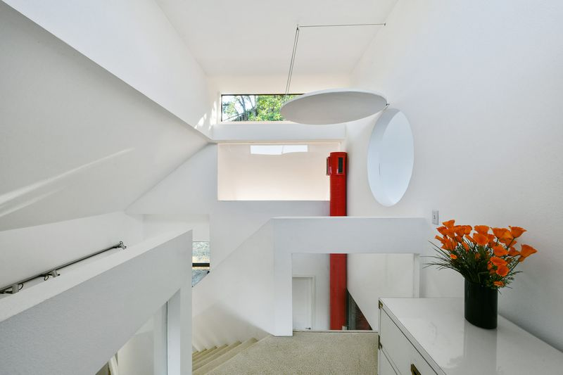 An open and airy room painted all white, with a staircase nearby, red-painted duct pipe and a circular cutout.