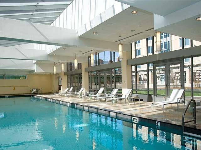An indoor pool with a lounge area and high ceilings.