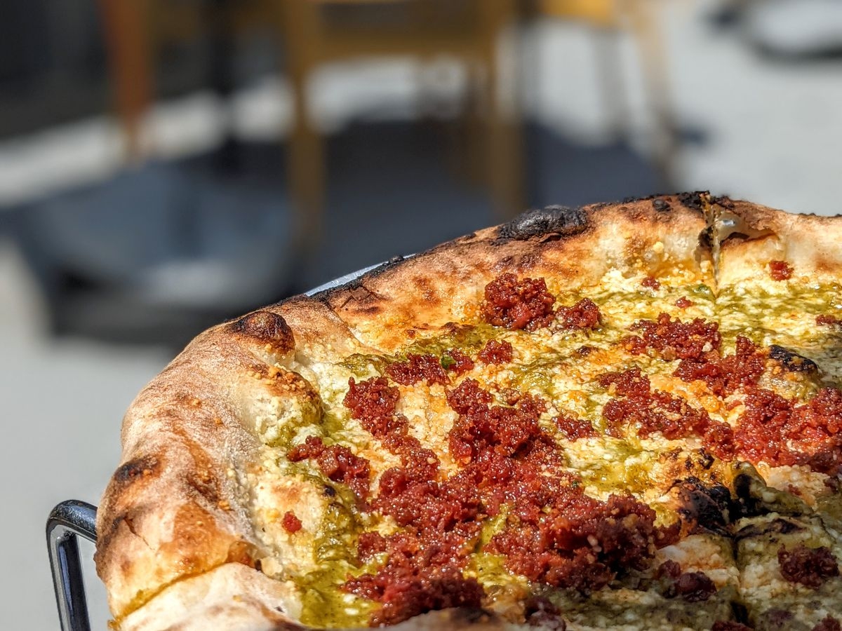 Closeup view of a pizza topped with crumbled chorizo and a green sauce. Patio furniture is visible in the background.