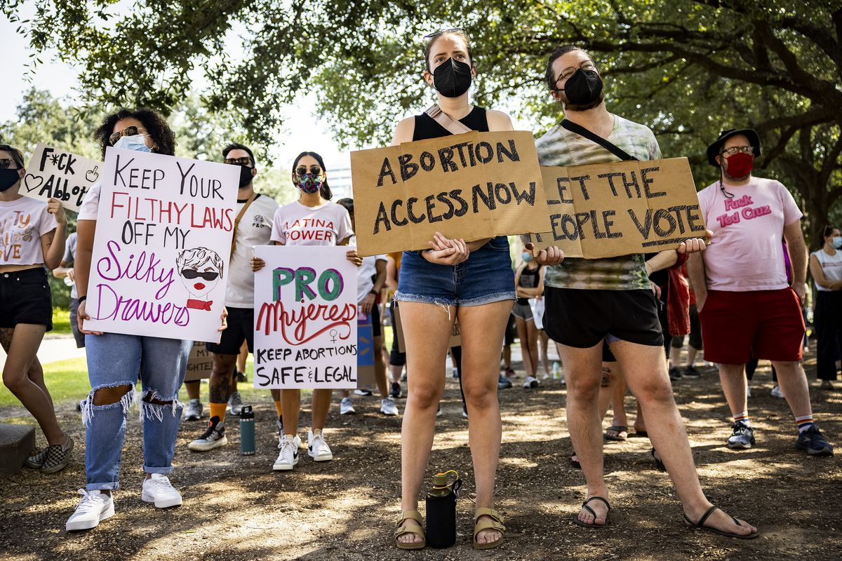 """Protesters hold signs reading, """"Abortion access now,"""" """"Let the people vote,"""" and """"Keep your filthy laws off my silky drawers."""""""