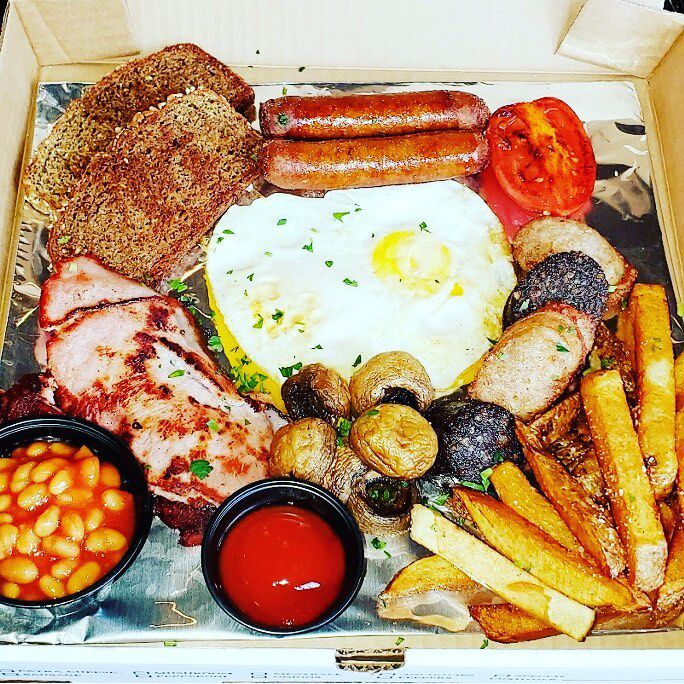 Overhead view of a breakfast spread in a takeout box: eggs, sausage, fries, beans, and more.
