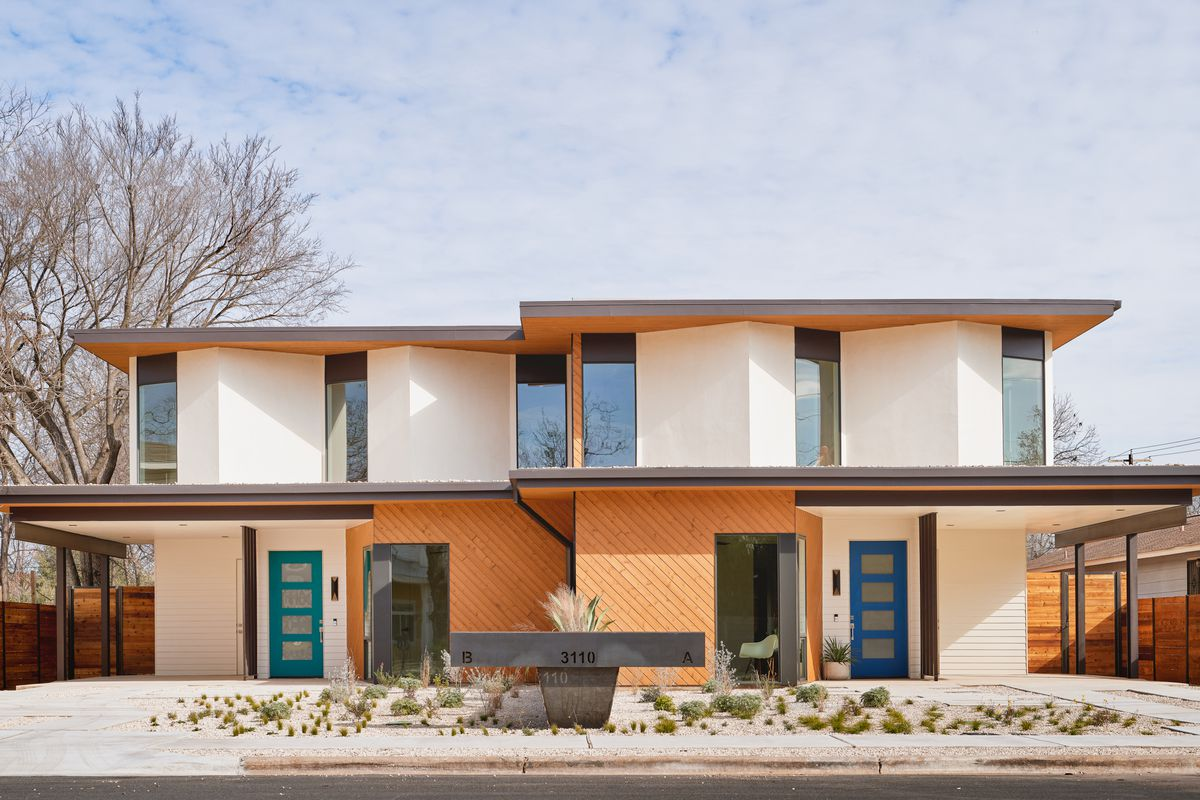 Photo of a contemporary new duplex exterior. It's a two-story building with a flat roof and flat overhands on the first floor. The front planes of both duplexes are staggered, creating a zigzag pattern.