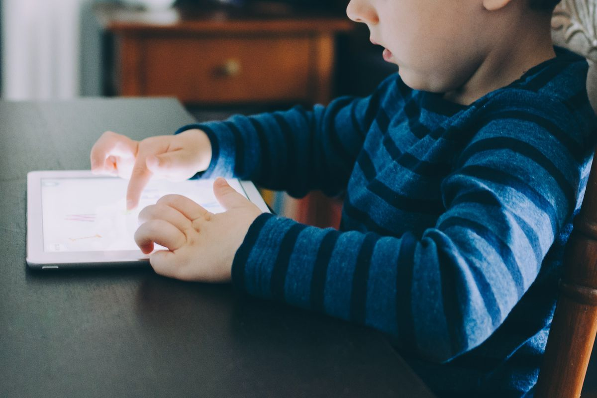 Young boy using a tablet.