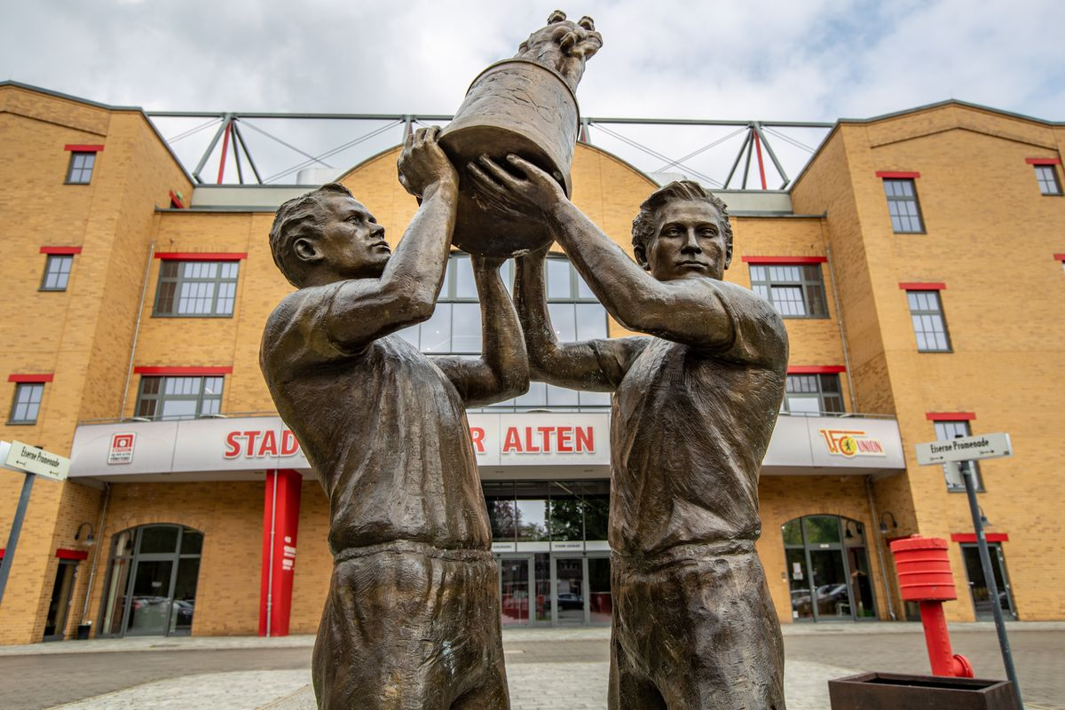 """29 April 2020, Berlin: A sculpture stands in front of the deserted main entrance to the stadium """"An der Alten Försterei"""", the home stadium of the 1.FC Union Berlin soccer club. Due to measures to contain the corona virus, no spectators are currently allowed into the stadium."""