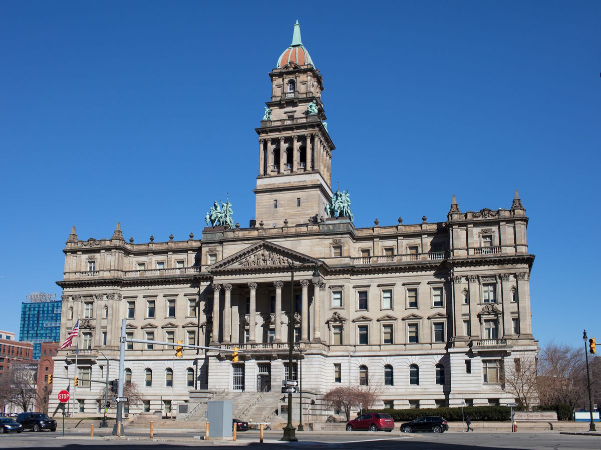 A Renaissance Revival stone courthouse with columns at the front entrance and copper statues on the roof.