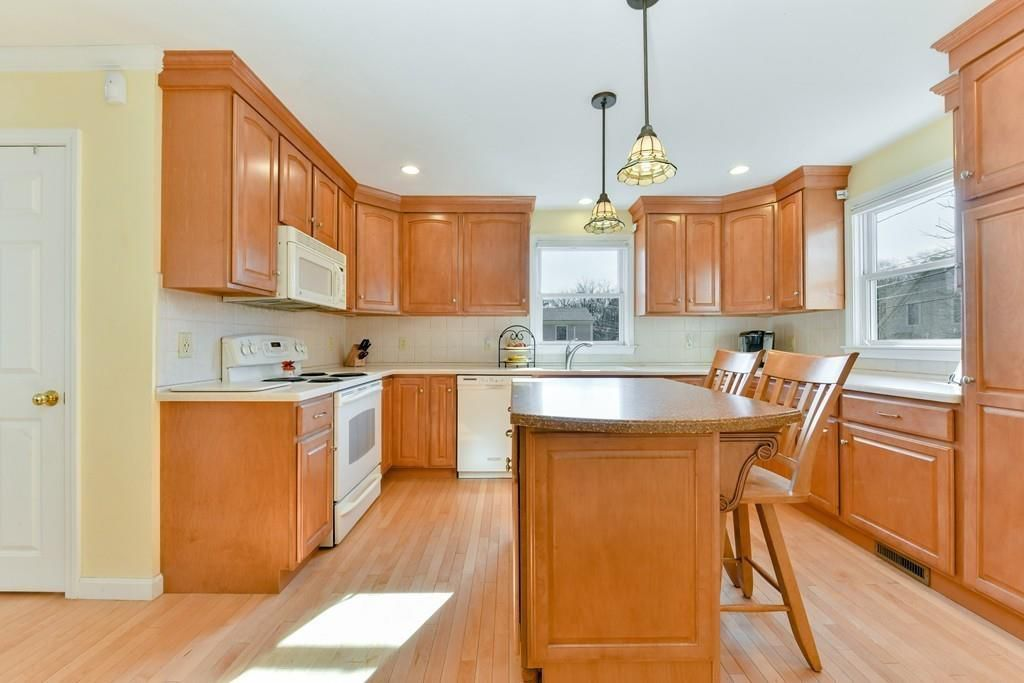 A kitchen with an island and lots of cabinetry.