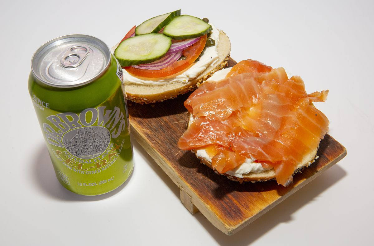Two sides of a sliced bagel, one with cream cheese and lox; the other with tomato, onion, and cucumber. A green can of Dr. Brown's Cel-Ray sits beside it.