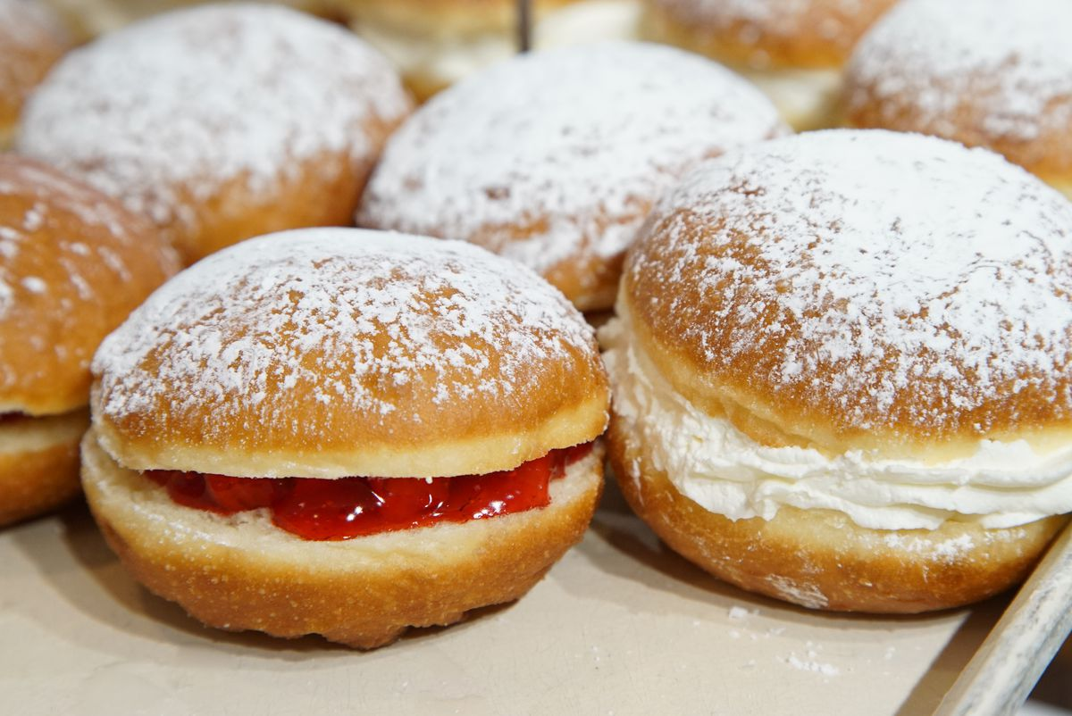 Rows of fluffy fried paczki filled with cream and topped with powdered sugar.