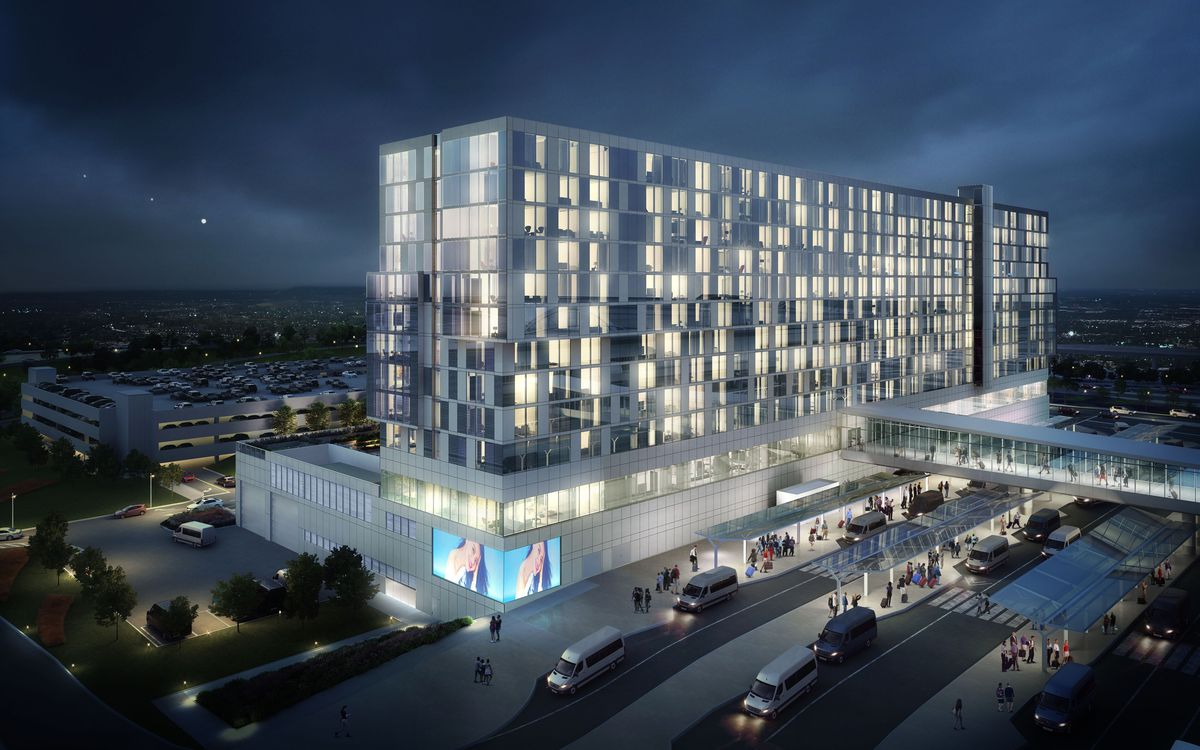A nighttime rendering shows the building lit up from the guest rooms and a light board at ground level.