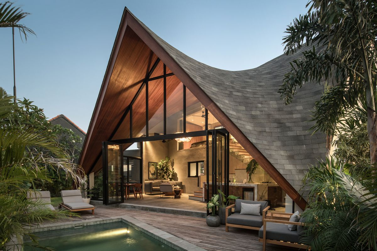 Sloped roof house with wall of windows and tropical plants.