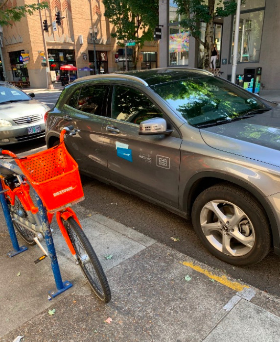 A bright orange bike-share bike is seen parked next to a grey car-share vehicle on a downtown Portland street.