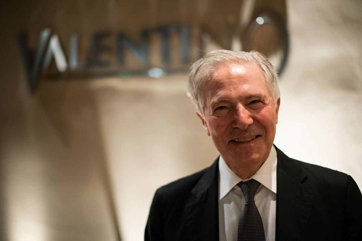 Piero Selvaggio wears a suit and tie in front of his restaurant Valentino's outdoor sign.
