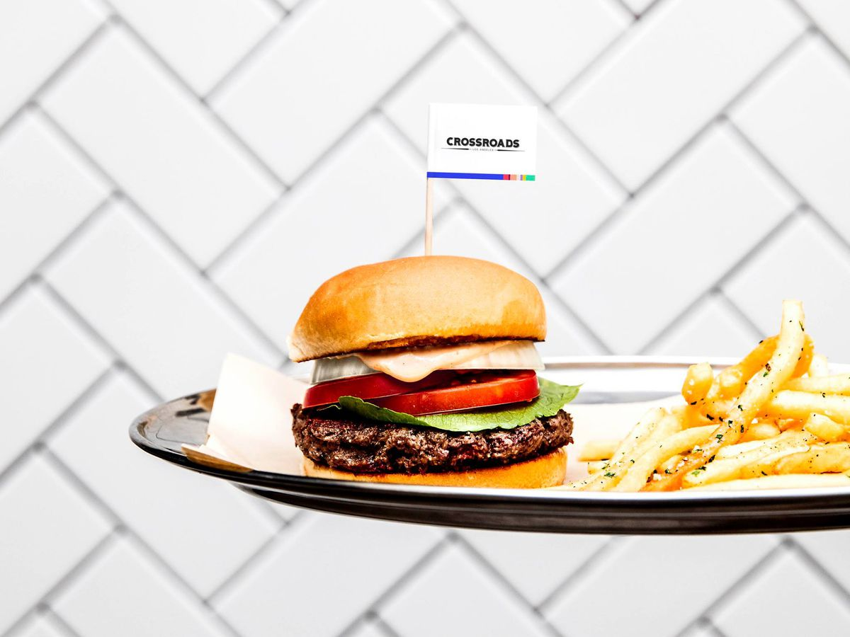 Crossroads Kitchen's burger on a plate with a small flag extruding from the top.