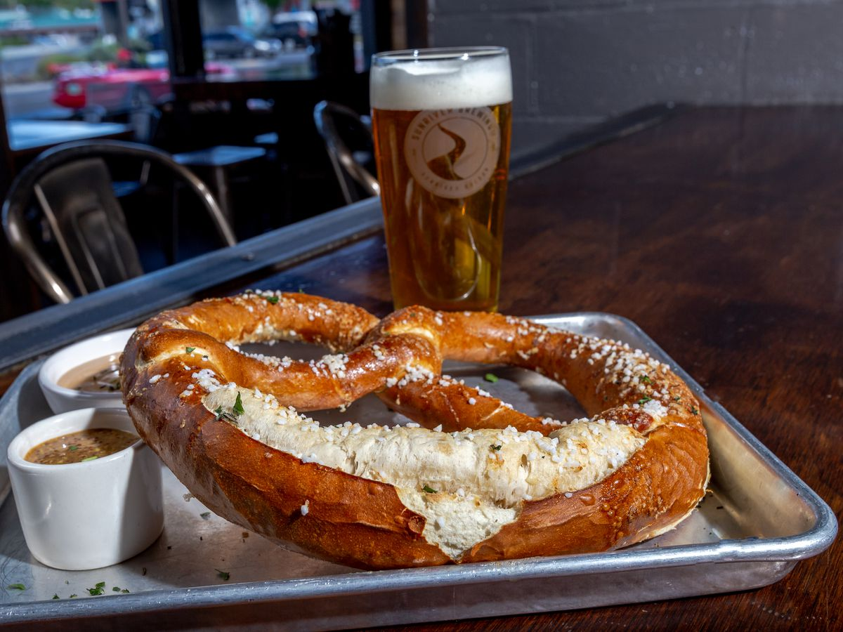 A beer sits next to a massive soft pretzel stuffed with cheese and dipping sauces at Sunriver Brewing